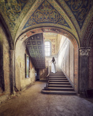 Christophe Dessaigne WOMAN ON STAIRCASE IN GRAND ORNATE HOUSE Women