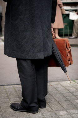 Colin Hutton BUSINESSMAN CARRYING BRIEFCASE ON CITY SIDEWALK Men