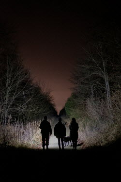 Colin Hutton SILHOUETTED TEENAGERS WITH DOG ON COUNTRY PATH Groups/Crowds