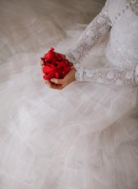 Nikaa WOMAN IN WEDDING DRESS HOLDING ROSE PETALS Women