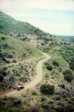Jill Battaglia CAR DRIVING ON TRACK IN MOUNTAINS Cars