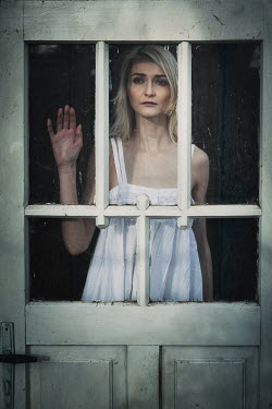 Magdalena Russocka sad woman behind old door