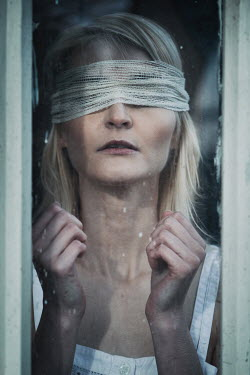 Magdalena Russocka close up of blindfolded woman behind old window
