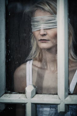 Magdalena Russocka blindfolded woman behind old window
