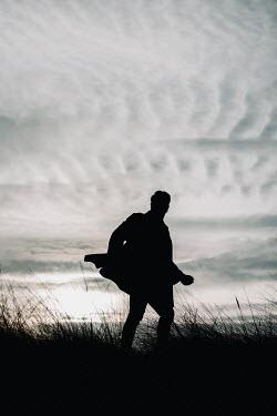 Rekha Garton SILHOUETTED MAN RUNNING IN FIELD AT DUSK Men