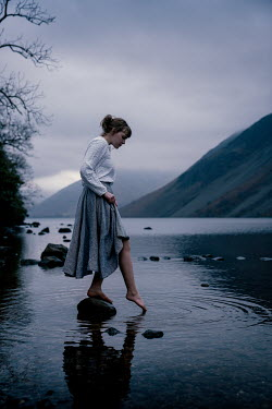 Rekha Garton Young woman in vintage dress standing on rock in river