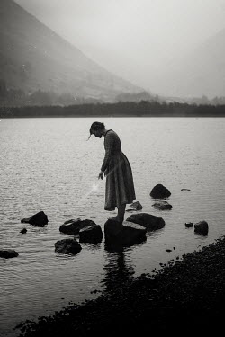 Rekha Garton Young woman in vintage dress standing on rocks in river