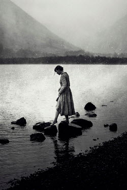 Rekha Garton Young woman in vintage dress walking on rocks in river