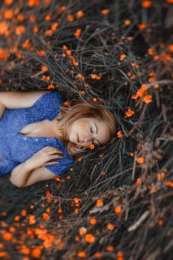 Shelley Richmond WOMAN LYING ON GROUND WITH ORANGE FLOWERS Women