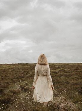 Shelley Richmond BLONDE WOMAN IN WHITE WALKING ON MOORLAND Women