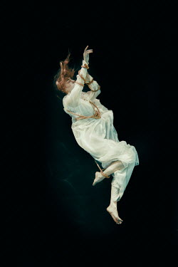 Rekha Garton Young woman in vintage dress tied with rope underwater