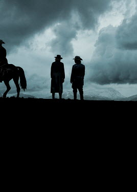 Stephen Mulcahey silhouetted cowboys with mountains at dusk Groups/Crowds