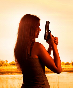CollaborationJS CLOSE UP OF WOMAN HOLDING GUN BY RIVER Women
