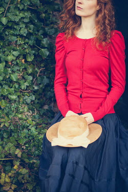Marie Carr Young woman in red sweater holding straw hat by ivy