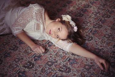 Anna Rakhvalova Young woman in lace dress lying on carpet