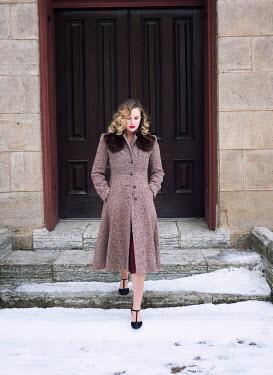 Elisabeth Ansley Woman in vintage coat walking on steps in winter