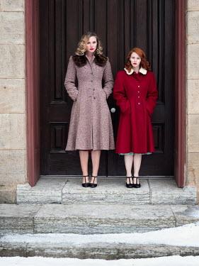 Elisabeth Ansley Women in vintage coats standing on steps in winter