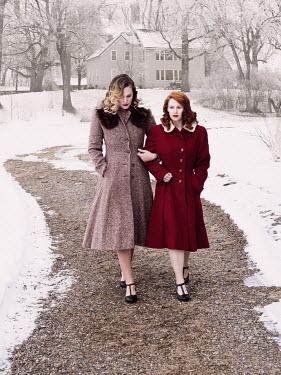 Elisabeth Ansley Women in vintage coats walking on park path in winter