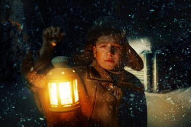 Kirill Sakryukin Teenage boy holding lantern in snow