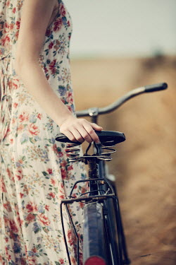 Magdalena Russocka close up of woman with bike standing in countryside