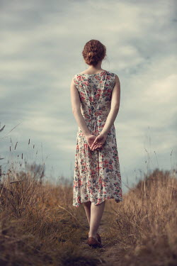 Magdalena Russocka woman in floral dress standing in countryside