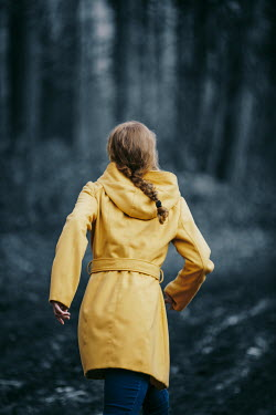 Magdalena Russocka modern woman in yellow coat running in forest