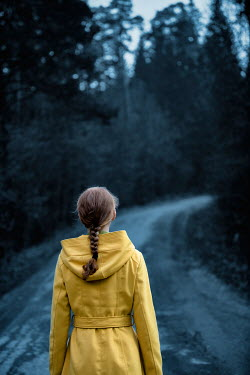 Magdalena Russocka Woman with yellow coat standing on road in forest