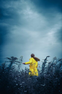 Magdalena Russocka Woman with yellow coat running in field