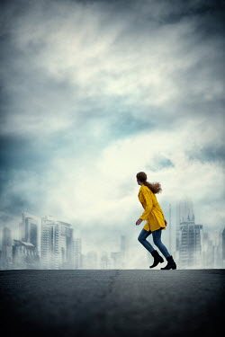 Magdalena Russocka Woman with yellow coat running on hill with cityscape
