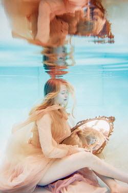 Rekha Garton Young woman in vintage dress holding mirror underwater