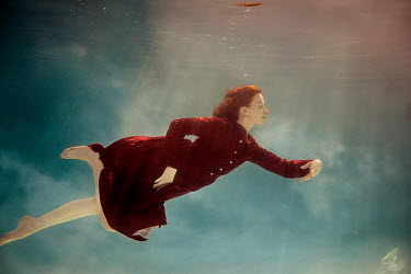 Rekha Garton Young woman in red vintage dress swimming underwater