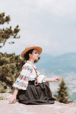 Muna Nazak Young woman in straw hat sitting on cliff Women