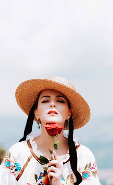 Muna Nazak Young woman in straw hat holding red rose Women
