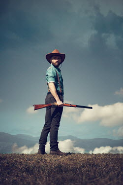 Magdalena Russocka COWBOY HOLDING RIFLE IN SUMMER LANDSCAPE Men