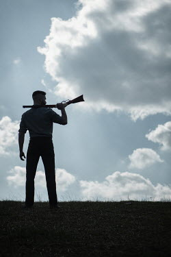 Magdalena Russocka silhouette of man with rifle standing in field