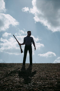 Magdalena Russocka man with rifle standing in field