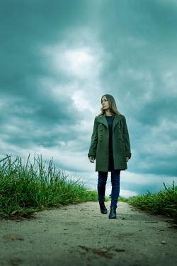 Stephen Mulcahey WOMAN IN COAT WALKING ON COUNTRY PATH Women