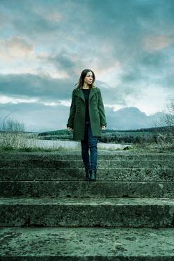 Stephen Mulcahey WOMAN IN COAT ON STEPS BY LAKE Women