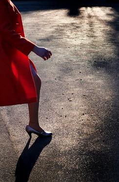 Ute Klaphake Woman in red coat walking on road at sunset Women