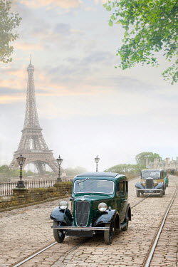 Lee Avison vintage cars driving on a cobbled road with Eiffel Tower 1940s Paris