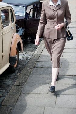Lee Avison 1940s woman walking past vintage cars