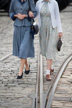 Lee Avison TWO RETRO WOMEN WALKING ARM IN ARM ON COBBLED STREET Women
