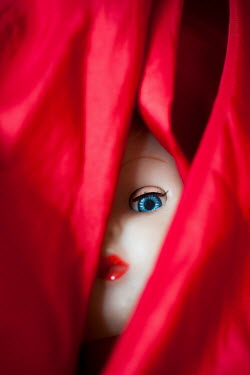 Lee Avison eye of a vintage doll behind red fabric