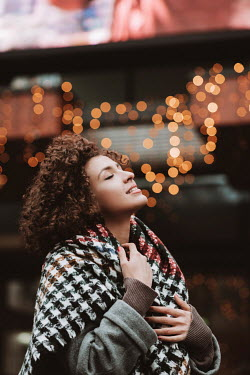 Muna Nazak HAPPY BRUNETTE WOMAN OUTDOORS WITH GLOWING LIGHTS Women
