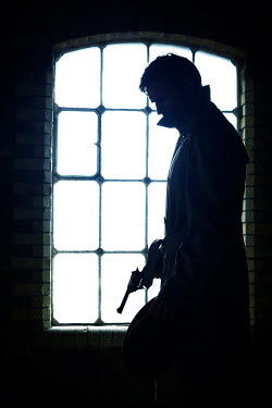 CollaborationJS silhouetted man holding gun by window Men