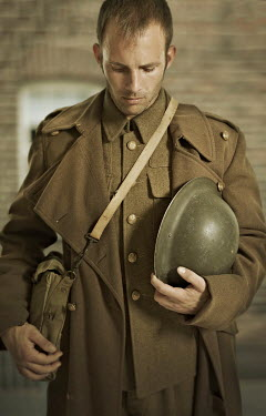 CollaborationJS A ww1 soldier looking  sad holding a helmet