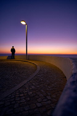 Chris Reeve MAN STANDING BY LAMPPOST WATCHING SEA AT SUNSET Men
