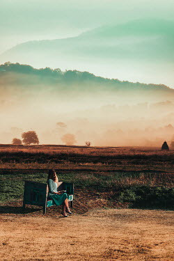 Dragan Todorovic WOMAN SITTING ON BENCH IN HAZY COUNTRYSIDE Women