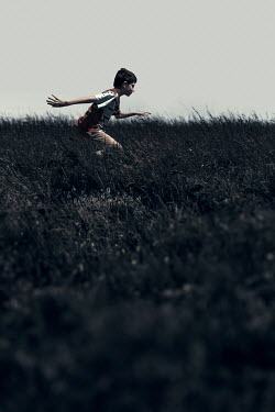 Dragan Todorovic BOY WITH DARK HAIR RUNNING IN FIELD IN SUMMER Children
