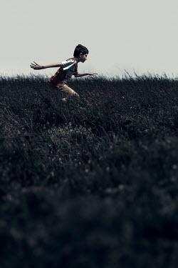 Dragan Todorovic BOY WITH DARK HAIR RUNNING IN FIELD IN SUMMER Children